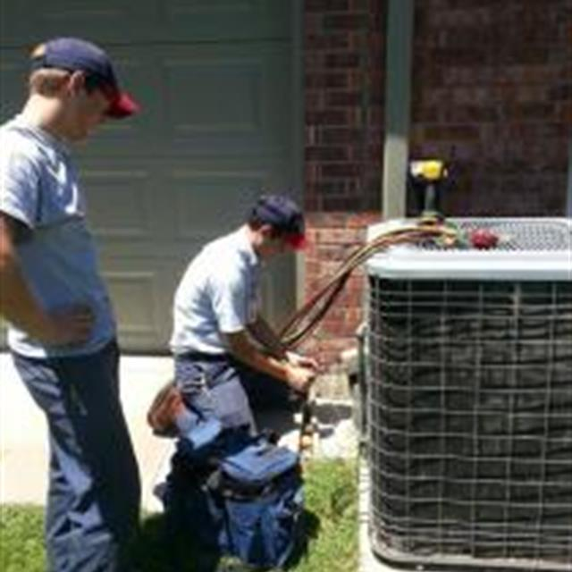Service tech Jordan repairs an Aire Serv customers A/C unit, while apprentice Colton hands him tools