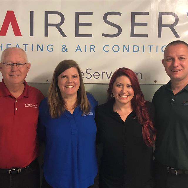four people in front of aire serv sign