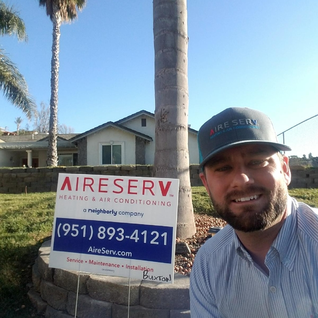 man smiling in front of Aire Serv sign