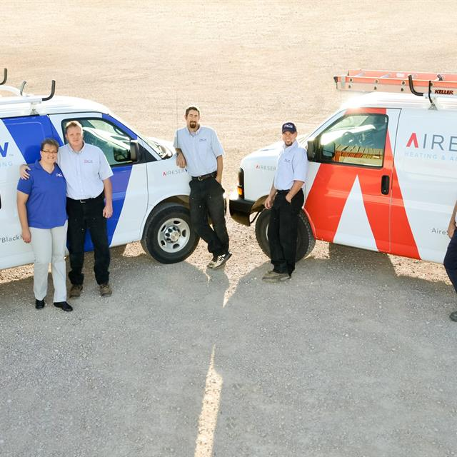 Team standing in front of aire serv vans