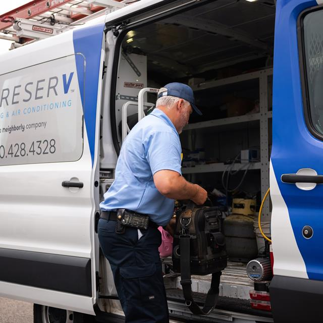 Employee putting tools into aire serv van